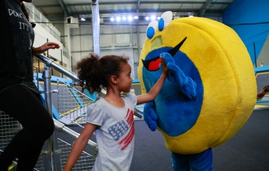 A girl high-fiving the Oxygen mascot in a family bounce session
