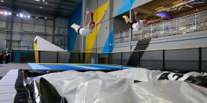 Two people jumping synchronised in trampoline park.