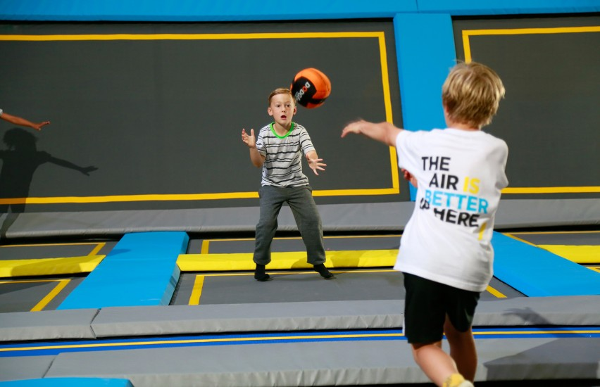 boy catching dodgeball at trampoline park
