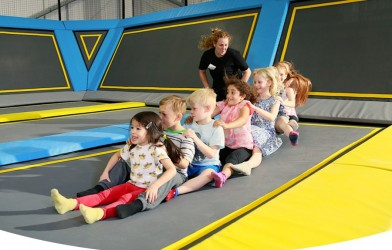 Kids do a human train on trampoline smiling