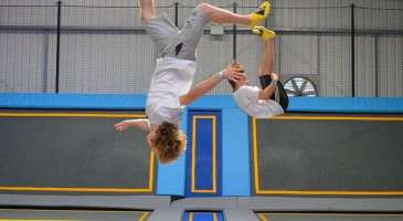 Two boys somersaulting on trampolines