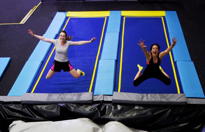 Two girls at company away day jumping at a trampoline park
