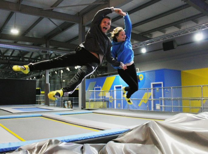 Couple holding hands jumping on trampoline in trampoline park