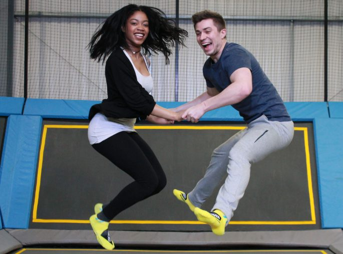 Two people holding hands jumping in a trampoline park
