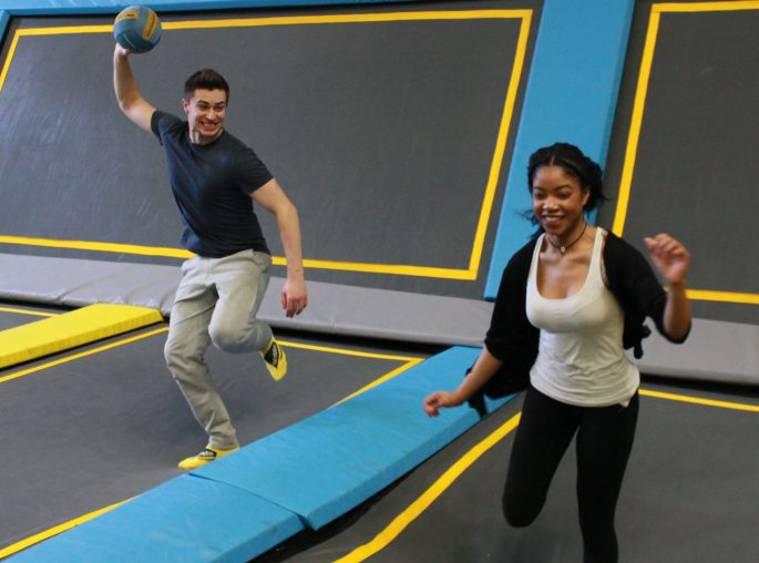Man in trampoline park throwing a dodgeball at a girl laughing