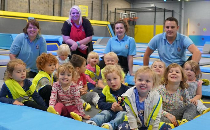 Toddlers sitting on trampolines at trampoline park party