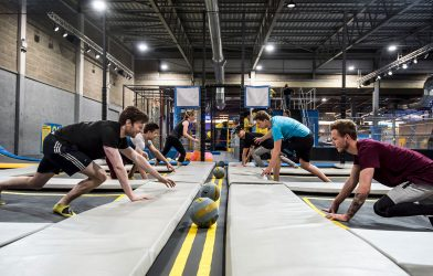 Adults playing dodgeball in trampoline park