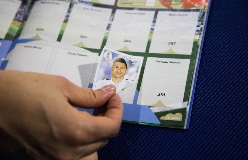 Person sticking a sticker in a World Cup sticker book